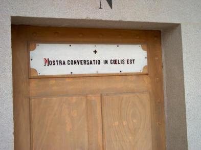 Cellule uniquement identifiée par une lettre (ici, «N») avec pensée religieuse sur la porte.